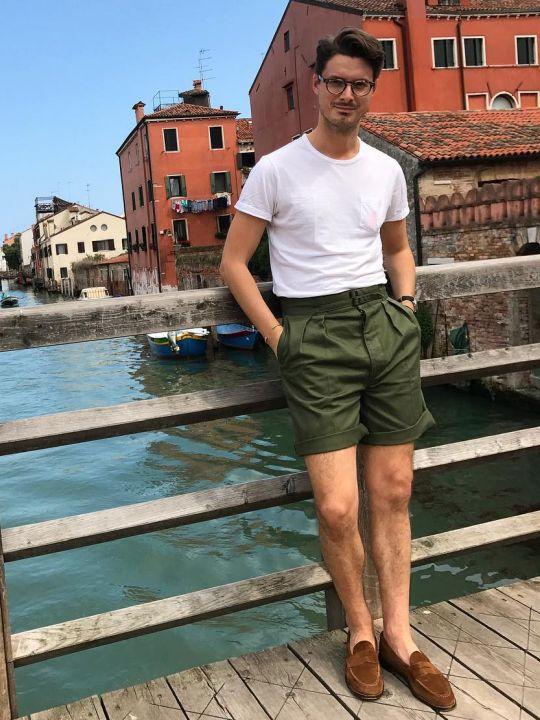 Vyras vilki baltus marškinėlius, žalius šortus, avi rudus batus