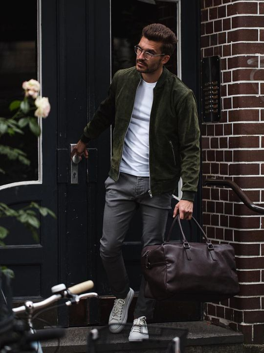 Vyras vilki tamsiai žalią bomber striukę, baltus marškinėlius, pilkus džinsus, avi baltus sportinius batelius