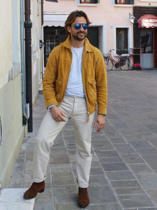 Vyras vilki geltoną striukę, baltus marškinėlius, šviesias kelnes, avi rudus batus