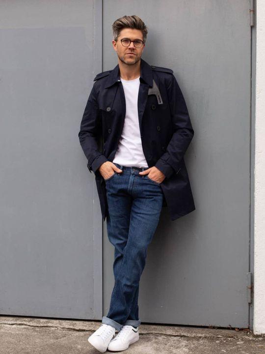 Vyras vilki juoda lietpaltį, baltus marškinėlius, mėlynus džinsus, avi baltus sportinius batelius