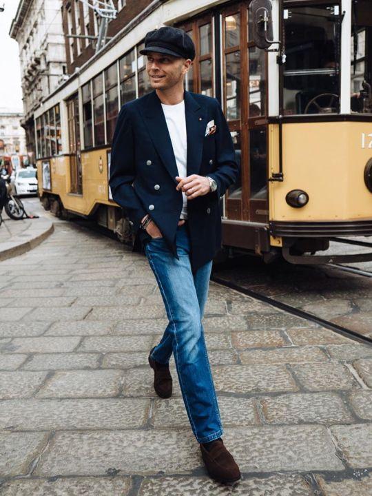 Vyras vilki tamsiai mėlyną švarką, baltus marškinėlius, mėlynus džinsus, avi tamsiai rudus batus