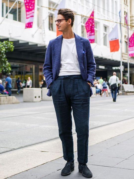 Vyras vilki mėlyną švarką, baltus marškinėlius, tamsiai mėlynas kelnes, avi tamsiai mėlynus batus