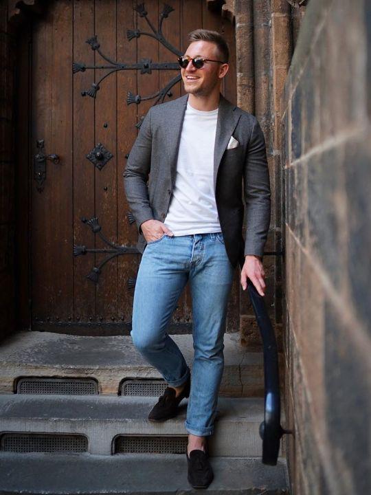 Vyras vilki pilką švarką, baltus marškinėlius, šviesiai mėlynus džinsus, avi tamsiai rudus batus